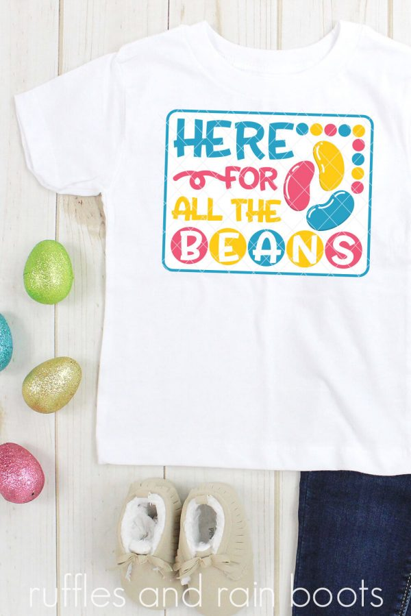 eggs and child outfit on wood background with here for the jelly beans svg in vinyl