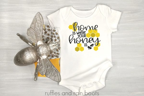 horizontal image of white onesie on wood background with bee and home is where your honey is svg in vinyl