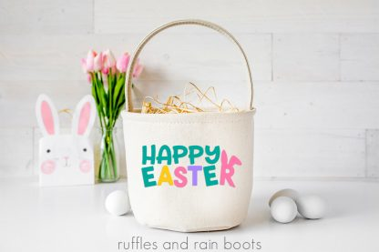 holiday scene on white wood with colorful happy Easter in vinyl on canvas Easter basket
