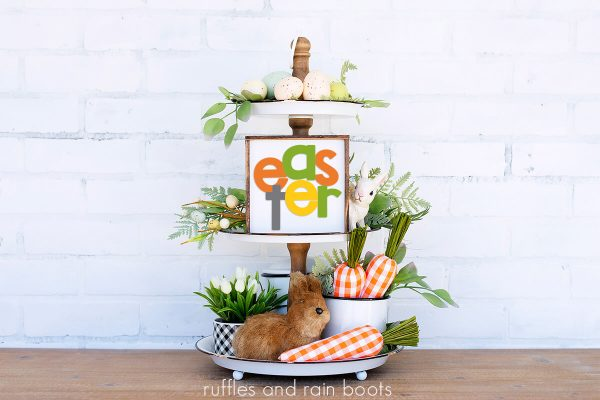 tiered tray on white background featuring Easter sign, bunny, fabric carrots, and greenery