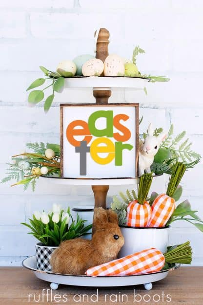 bright vertical image of tiered tray with carrots, greenery, bunny, and Easter SVG with cross on square sign
