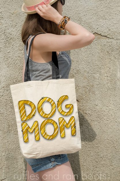 vertical image of woman with tote bag decorated with mustard and yellow animal print sublimation of dog mom