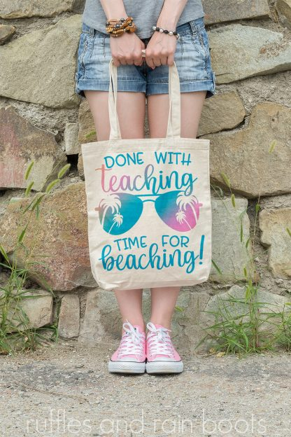 vertical image of woman in front of rock wall holding tote bag with done with teaching time for beaching in pink and blue sublimation print