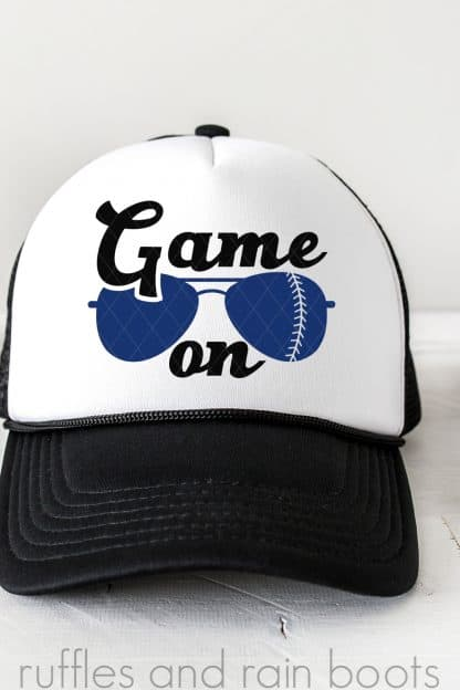 vertical image of white and black trucker hat with game on baseball svg with sunglasses on white background