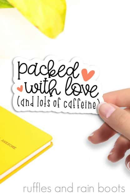 close up image of woman holding packed with love and caffeine sticker for small business