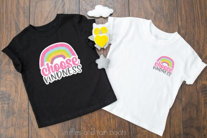 horizontal image of black and white t shirts on wood background with choose kindness svg with rainbow in pink blue green yellow and purple