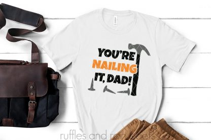 bag pants and white t shirt on white wood background with black gray and orange Father's Day SVG which says you're nailing it dad
