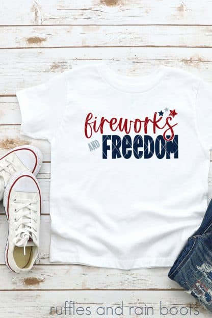 close up of white t shirt on white wood background with fireworks and freedom in red and blue