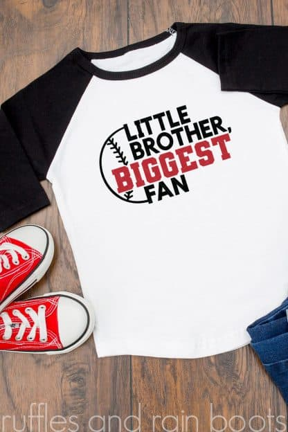 vertical image of white and black raglan tee shirt with black and red little brother biggest fan baseball svg in center