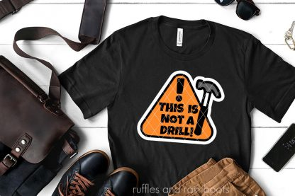 orange and black this is not a drill on black t shirt with white offset on white wood background