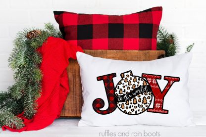 horizontal image of JOY Christmas sublimation with leopard print on white pillow on holiday bench