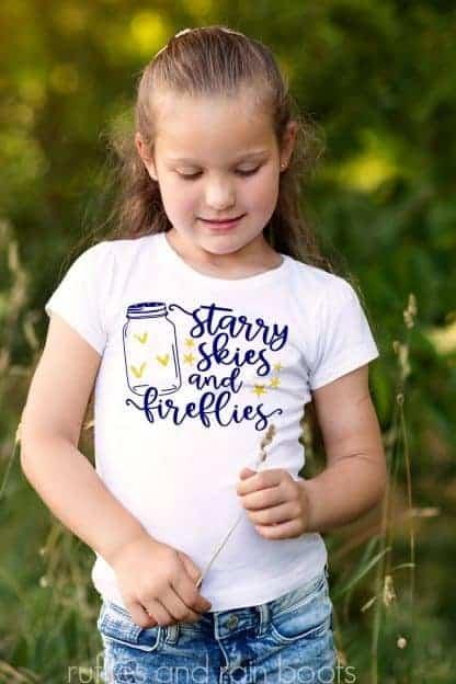 child wearing a shirt featuring a Summer SVG Starry Skies Fireflies