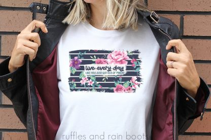 woman in white t shirt holding open black jacket with live every day like you just got out of prison sublimation in navy stripe and pink floral background