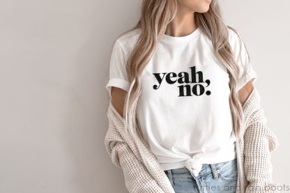 horizontal image of beige wall with woman in sweater and white t shirt with yeah no svg in bold design in black vinyl made on cricut