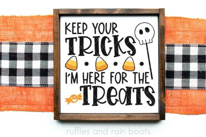 horizontal image of orange and buffalo check burlap with Halloween sign that says keep your tricks I'm here for the treats in black orange and yellow