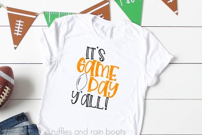 white t shirt with its game day yall svg for football fans in black and orange on white wood background with a football banner