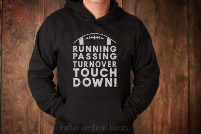 horizontal image of man in black hoodie in front of wood wall with gray vinyl running passing turnover touchdown football svg on shirt