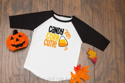 horizontal image of wood background with halloween svg candy corn cutie in black orange and yellow on black raglan sleeve shirt