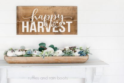 horizontal image of wood plank with white happy harvest svg in painted stencil vinyl hanging on white wood plank wall with pumpkins and greenery for fall decor