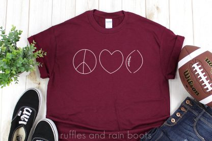 horizontal of maroon t shirt with elegant minimalist peace love football svg in white vinyl on a white wood background with football jeans and tennis black tennis shoes