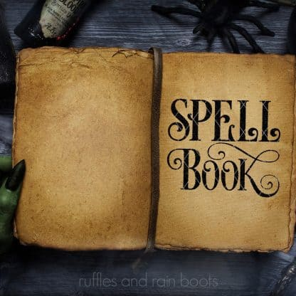 horizontal image of spell book svg in black textured vinyl on old book in witch hand on halloween background