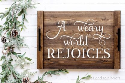 horizontal image of a weary world rejoices in white vinyl on a Christmas tray in dark wood placed on a holiday greenery background