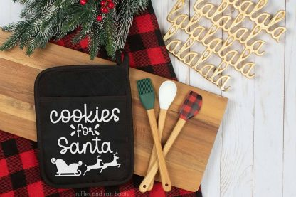 horizontal image of black pot holder on Christmas kitchen background with white HTV vinyl on black potholder with cookies for santa svg with sleigh and reindeer