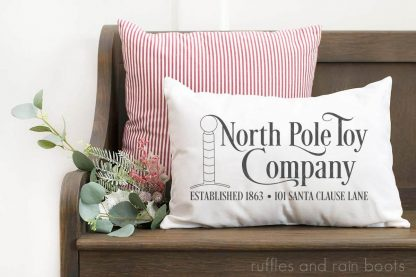 horizontal image of white pillow with north pole toy company in HTV vinyl cut with Cricut machine on wood bench in front of holiday greenery and red and white ticking stripe pillow
